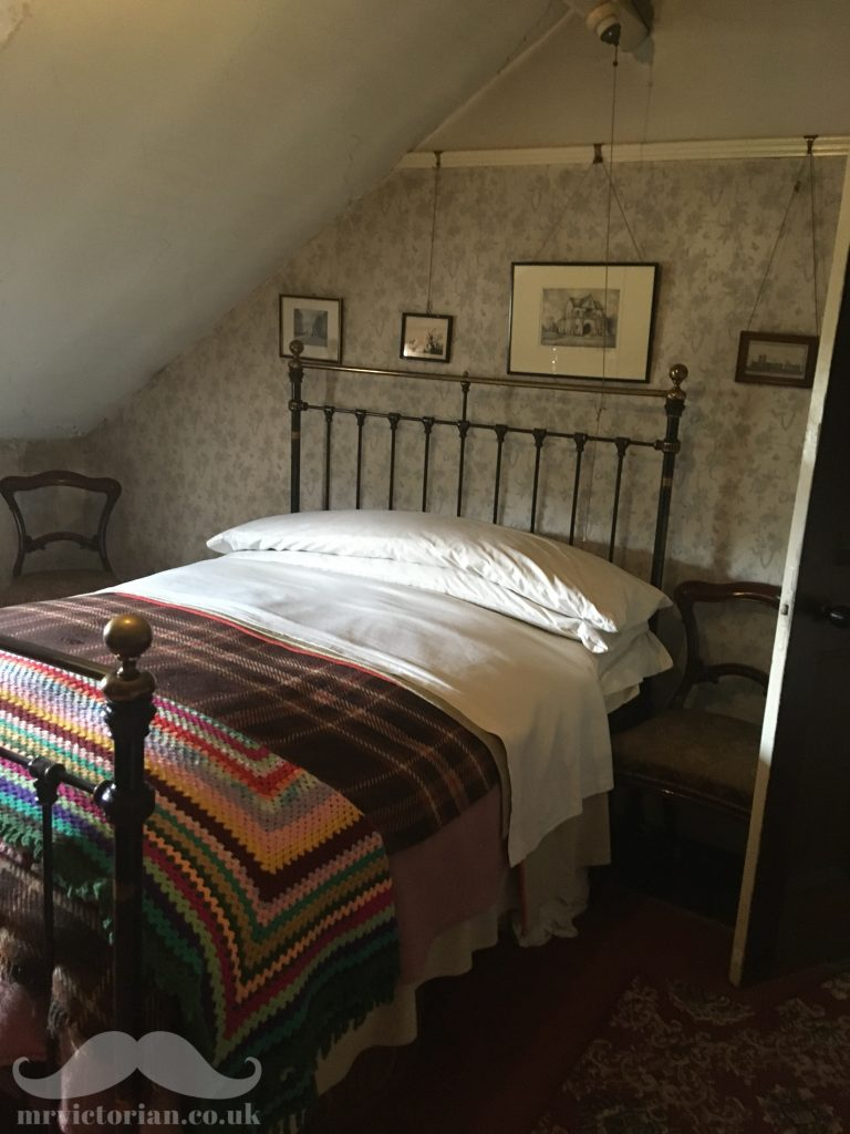 Mr Straw's House bedroom featuring brass and iron bed