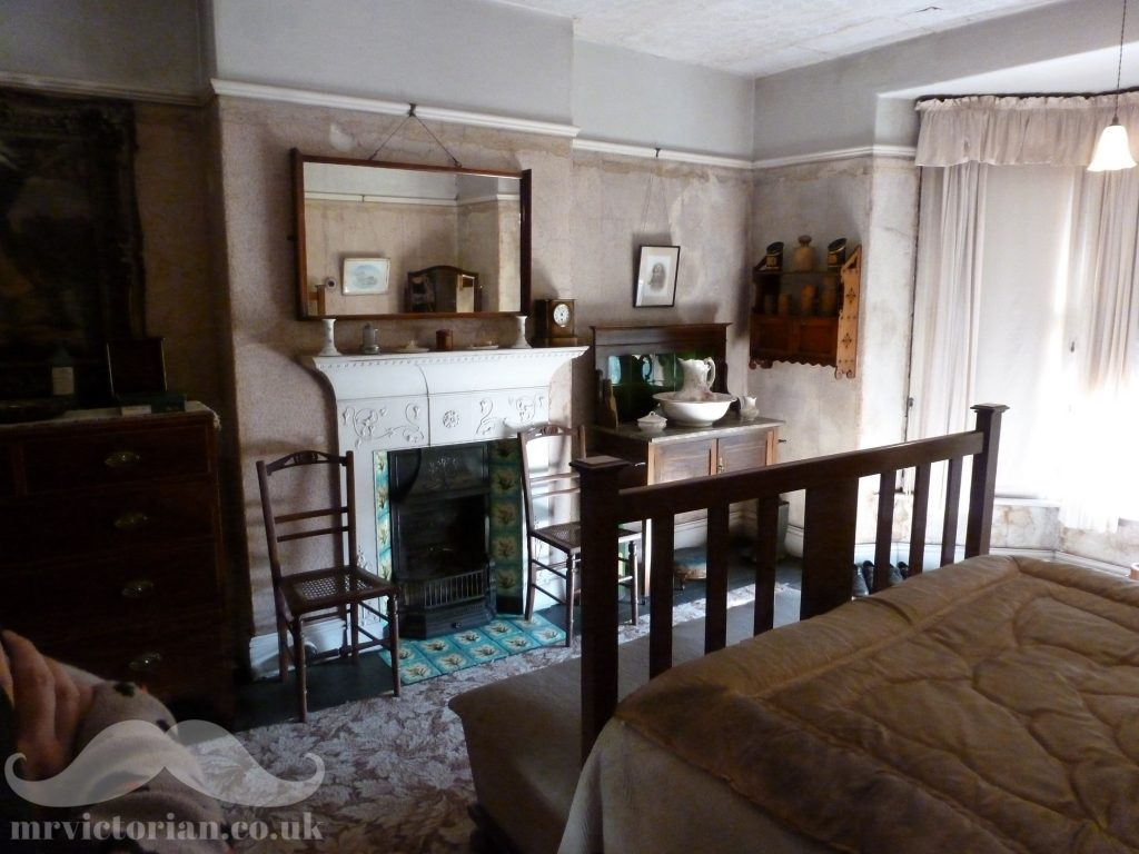 Mr Straw's House bedroom featuring  Edwardian tiled fireplace