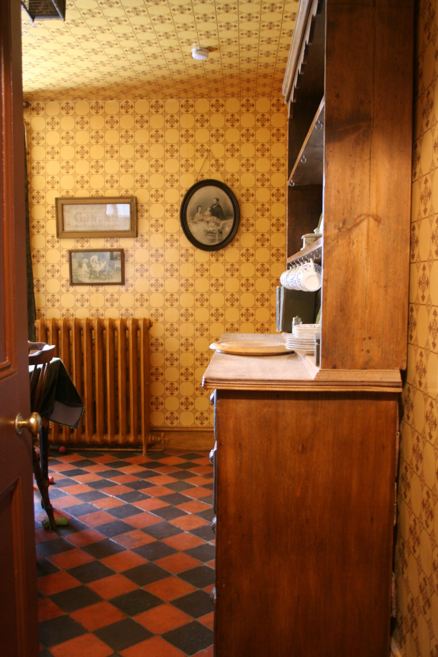 Modern conveniences - woodgrained radiator in my Victorian kitchen showing quarry tiled floor and dresser